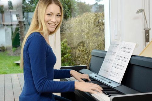Frau spielt E-Piano