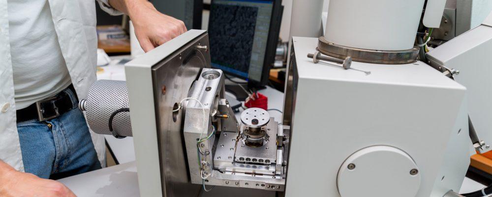 Mann arbeitet mit einem Elektronenmikroskop