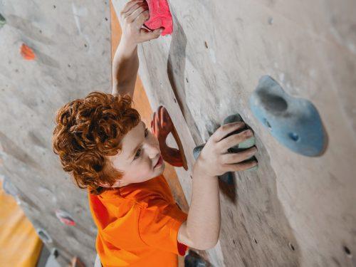 Kleiner Junge beim Bouldern