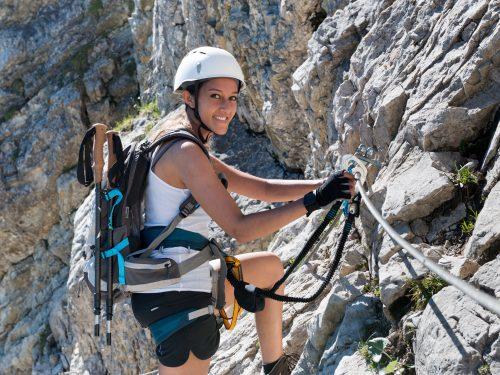 Frau an einem steilen Klettersteig
